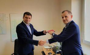 Tauragės rajono savivaldybės Švietimo ir sporto skyriaus vedėjas Egidijus Šteimantas, ir UCS Baltic direktorius Darius Simanavičius spaudžia rankas